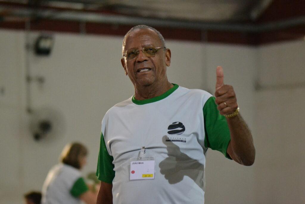 Senhor João Maia olha para a câmera e faz sinal de positivo com a mão. Ele utiliza camiseta vermelha e verde com o logotipo do Instituto Família Barrichello.